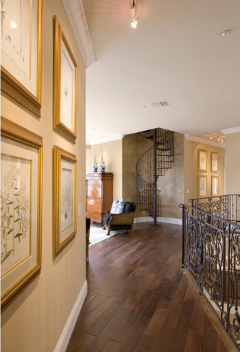 peach toned walls in home interior, wrought iron spiral staircase