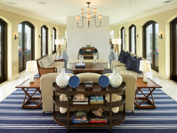 yellow living room, arched french doors, lots of natural light, white fireplace, blue striped rug