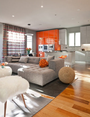 modern living area with bright orange kitchen cabinets