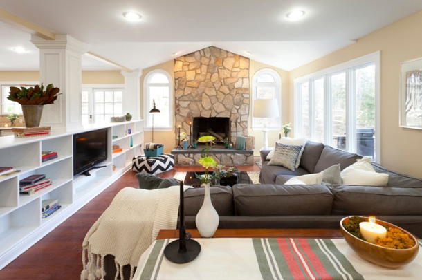 living room with purple-gray sectional, stone fireplace and white shelves
