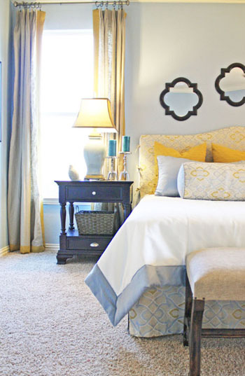 white bedroom, bright yellow pillows, black nightstand, blue accents