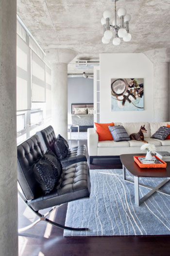 modern loft living room, light blue area rug, black leather barcelona chairs, white modern sofa, orange accents, lots of natural light