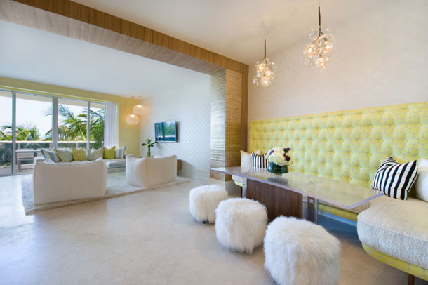 modern condo dining area, sheepskin ottomans, custom booth seat with light yellow upholstered back, cluster of globe pendants, clear top dining table with wood base