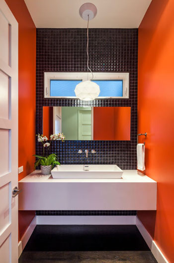 modern bathroom, bright orange paint, black pillow mosaic tile accent wall, horizontal linear mirror, wall mounted lavatory faucet, rectangular white vanity sink
