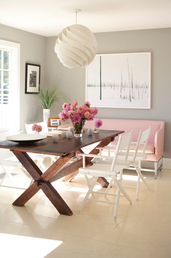 pale pink loveseat in dining room, dark wood farm table, light gray walls, white accents