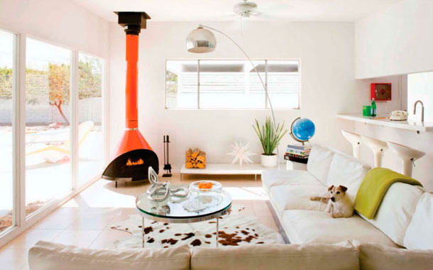 white living room with bright orange wood burning fireplace