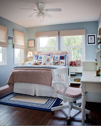 light blue kids bedroom, white desk and chair, white bedding, quilt patterned bedding, dark wood floor