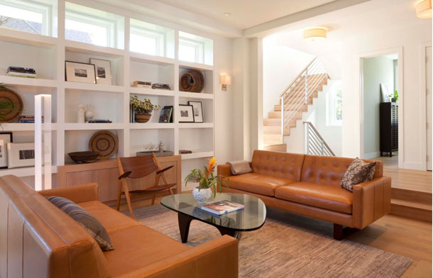 white living room, caramel leather sofas, built-in shelves, clerestory windows