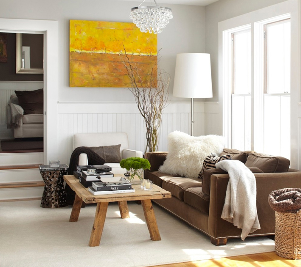 cool white living room, orange-yellow artwork, white trim, dried branches