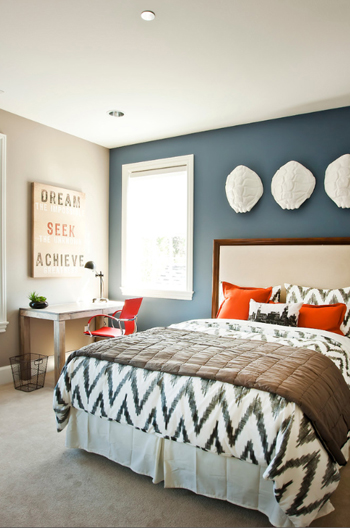 bedroom with slate blue accent wall, white trim, orange accents