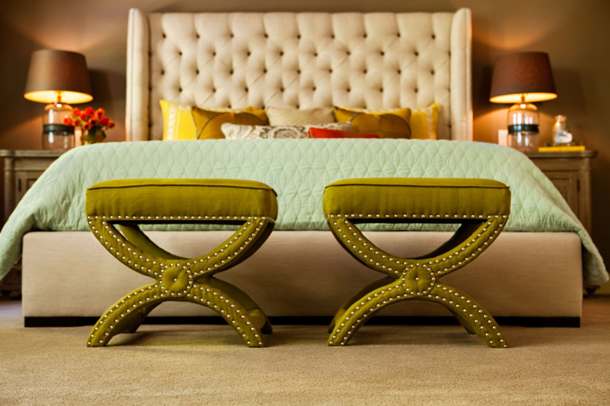 upholstered bed close-up with chartreuse ottomans