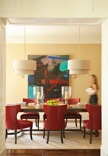 dining room with tan walls, red chairs, turquoise accents