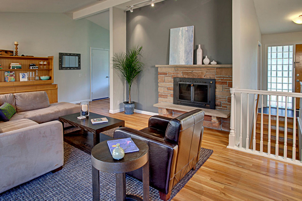 family room, gray accent wall, light wood floor, stone fireplace