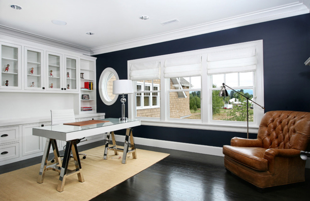 home office design, dark navy walls, white built-in cabinets, white trim, brown leather chair, modern saw-horse desk