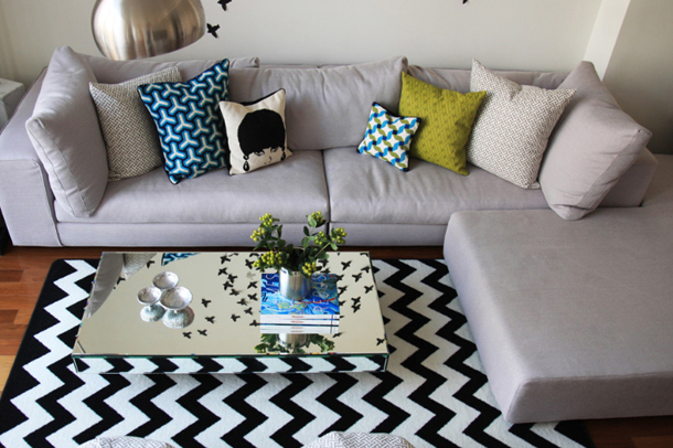 living room close-up, black and white chevron rug, light grey sectional, green-gold accent pillow