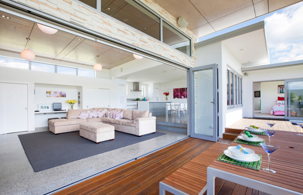 exterior sliding glass wall, warm wood deck, clerestory windows, grey and cream living room