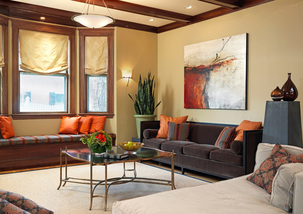 living room with light tan walls, orange accent pillows, dark wood trim,