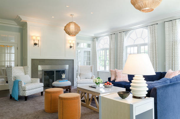 white living room with orange stools, navy blue sofa