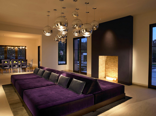 family room with dark puple sectional, dark purple fireplace surround, glass orb pendants
