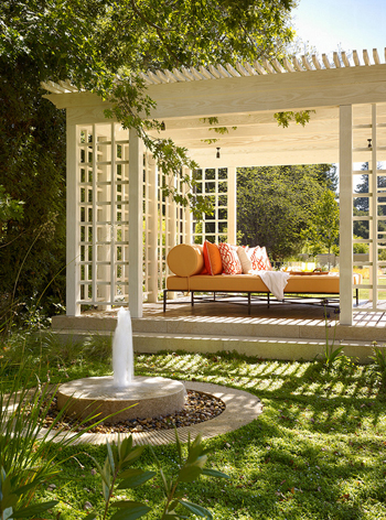 white pergola with orange chaise lounge