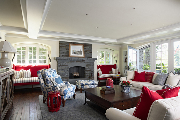 white living room with slate gray fireplace, bright red accents