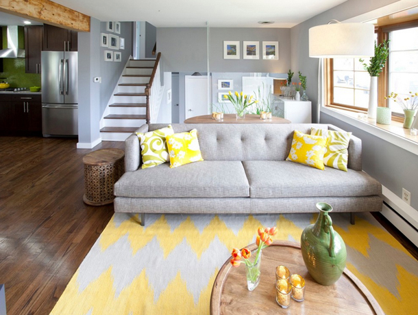 grey living room, bright yellow throw pillows, bright yellow and white chevron rug, dark wood floors