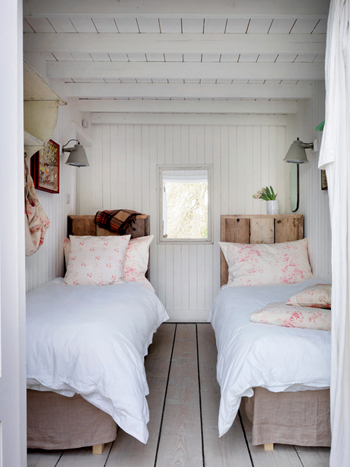 white cottage bedroom, two single beds, reclaimed wood headboards, pale gray wood floors, pink florwal pillowcases