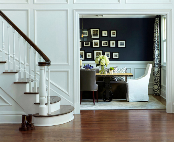 white wood paneled entry, cherry wood floors, curved staircase, dark royal blue dining room with white wainscoting