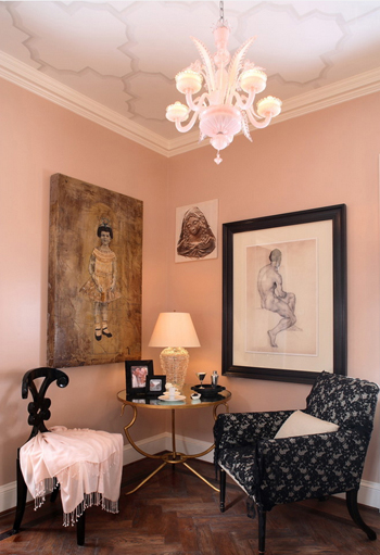 soft pink sitting area, wood floors, black painted chair with off-white throw, white accents, black accents