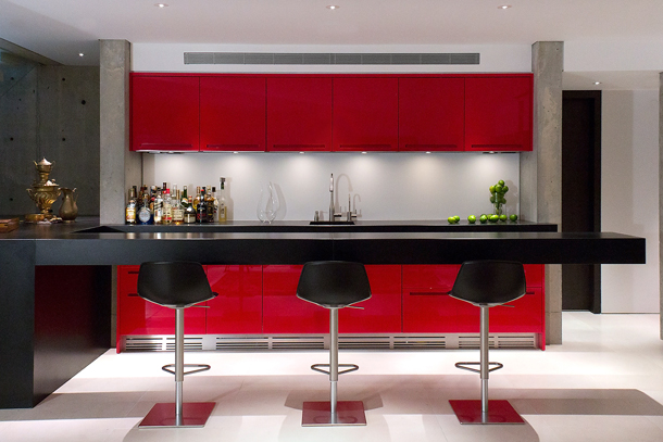 white kitchen with black counter and stools and red cabinets