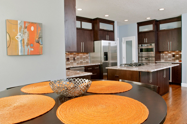 light blue kitchen, dark wood cabinets, glass cabinet doors, wood floors, round orange placemats