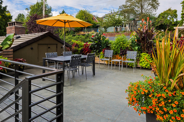 outdoor living area, butterscotch umbrella, orange flowers