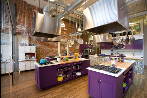 kitchen, deep purple cabinets, stainless steel range hoods, brick wall, wood floors, butcherblock countertop