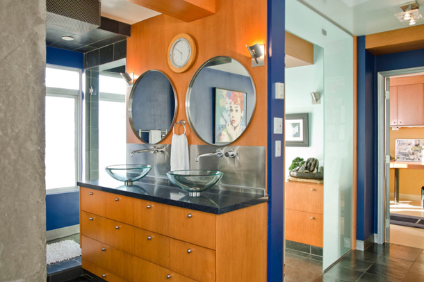 bathroom with royal blue paint, orange toned wood, round mirrors, glass vanity bowls