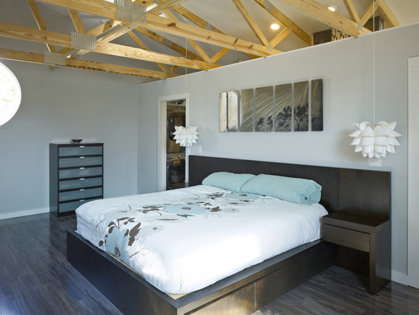 contemporary bedroom, exposed rafters, pale blue accents, dark wood furniture