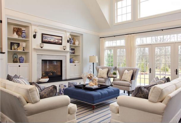 pale blue living room with white trim, blue square ottoman, striped rug