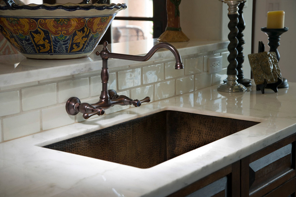 rustic brown rectangular kitchen sink, white countertop, white backsplash tile, wall mounted kitchen faucet