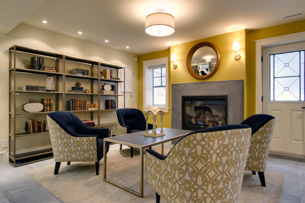 basement living room, bright gold accent wall, navy blue lounge chairs
