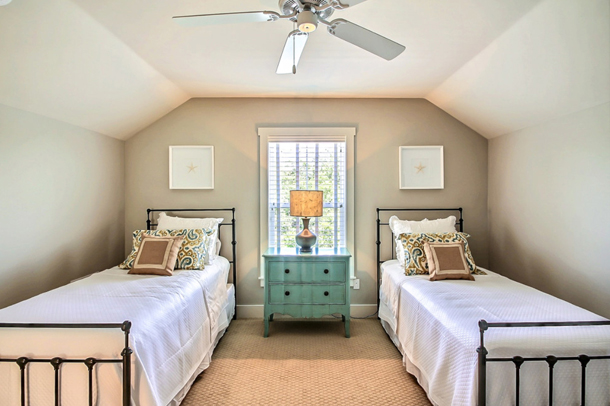 bedroom with two single beds, aqua blue nightstand, pale gray walls