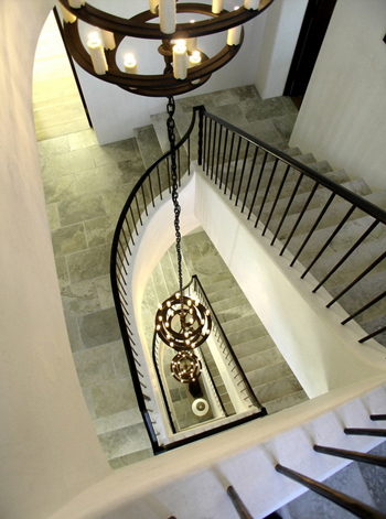 off-white staircase, gray-gree tile floors, black railing, multi-leveled chandelier