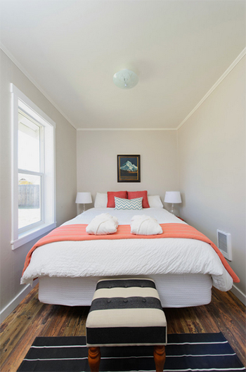 minimalist white bedroom with coral accents