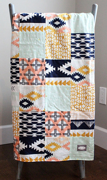 boldly patterned peach and navy baby quilt