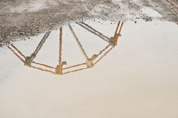 ferris wheel reflection in mud puddle