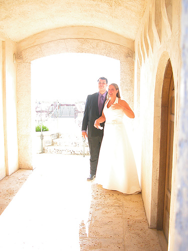 bride and groom posing outside western style building