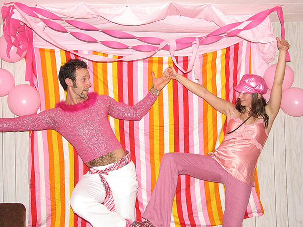 man-and-woman-posing-in-pink-and-orange-party