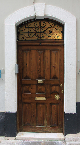 old brown paneled door with arched top