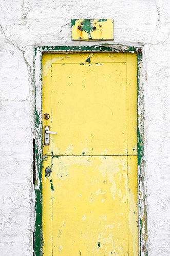 bright yellow door in old stucco wall