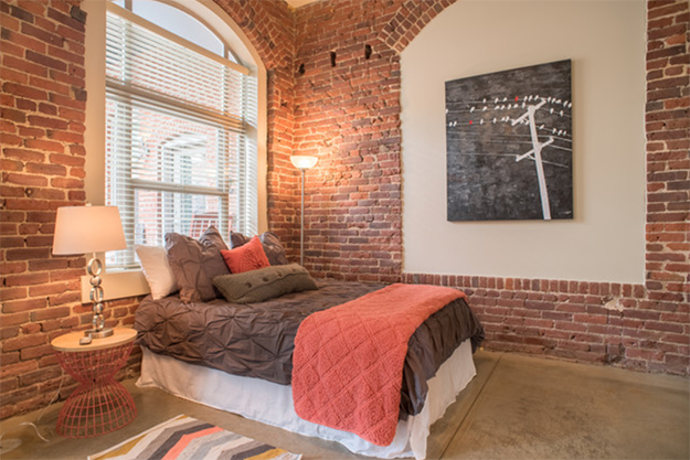 brick walled bedroom with pantone peach echo accents