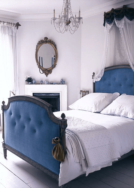 white bedroom with marine blue upholstered bed