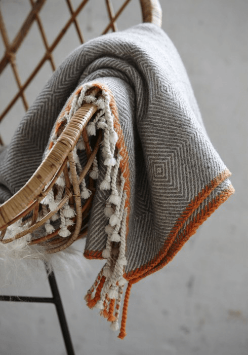 gray plaid throw blanket with burnt orange edge